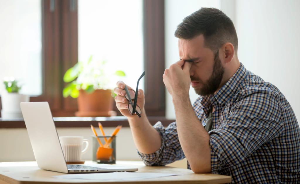 Hombre reflexionando en una mesa de trabajo